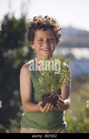 Young boy holding small plant - Stock Photo