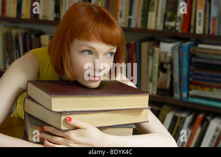 woman leaning on pile of books - Stock Photo