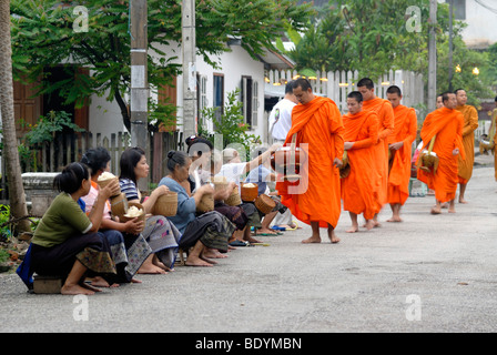 Morning alms collection, Thakbat of the monks and novices in the monasteries of Luang Prabang, men and women distributing - Stock Photo