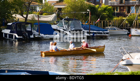 Two active senior couples in a rowing boat on the river Stour, Christchurch, Dorset. UK. - Stock Photo