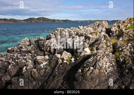 Isle of Iona Scotland - summer rocks sea and sand looking across Sound of Iona to Mull - Stock Photo