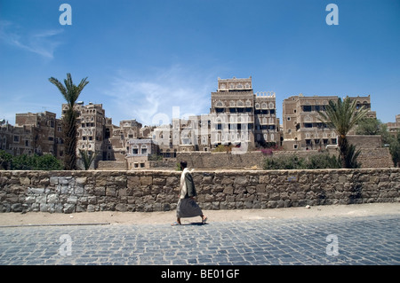 A man strolling past tower houses in a pedestrian area of the old city of Sana'a, Yemen. - Stock Photo