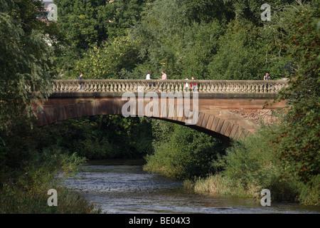 Pedestrians crossing a bridge in Kelvingrove Park in Glasgow's West End, Scotland, UK - Stock Photo