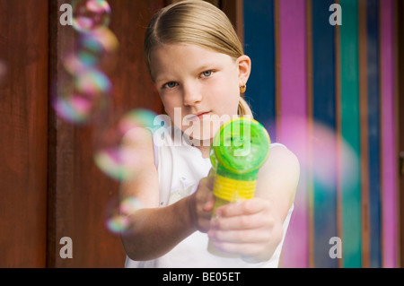 girl pointing bubble gun to camera - Stock Photo