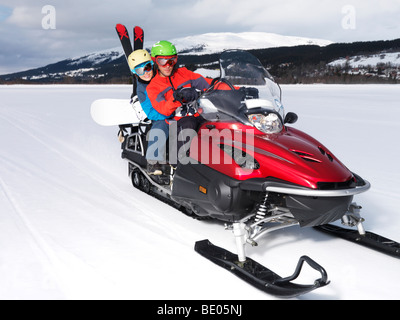 A couple riding a red skidoo. - Stock Photo