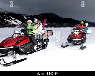 Two couples riding skidoos. - Stock Photo