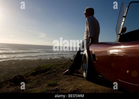 Older Man views sunset from car bonnet - Stock Photo