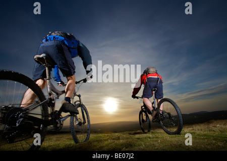 Two mountain bikers riding together. - Stock Photo
