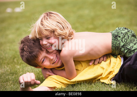 young boy wrestling with brother - Stock Photo