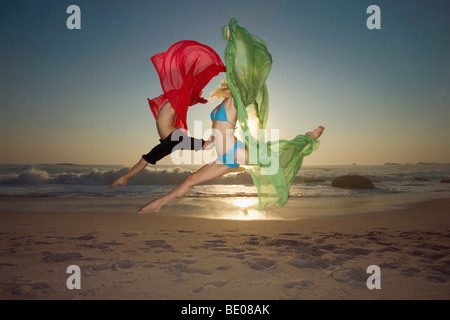 Dancers leaping on a beach - Stock Photo