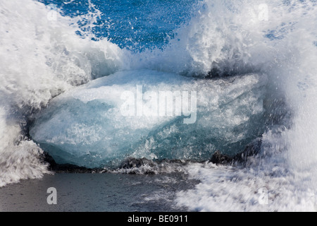 Slow shutter speed shot of a wave breaking against an iceberg on a volcanic black sand beach in Iceland. - Stock Photo