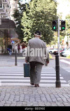 Elderly old man carrying a suitcase walking in a city using a green man road crossing NOT MODEL RELEASED EDITORIAL - Stock Photo