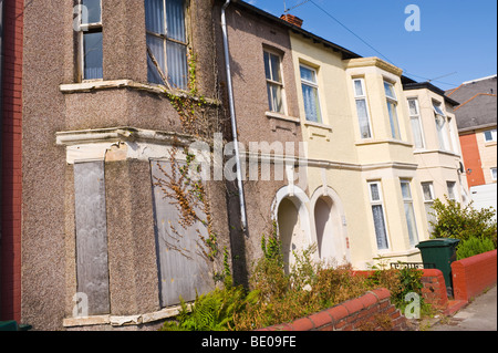 Derelict boarded up terraced house in Newport South Wales UK - Stock Photo