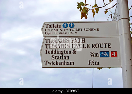 thames path and thames cycle route sign by the river thames at teddington lock, giving directions to twickenham - Stock Photo