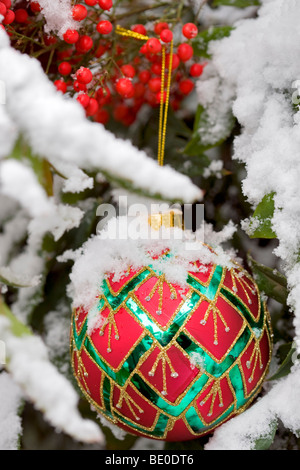 Christmas tree ornament in snow covered bush with red berries. - Stock Photo