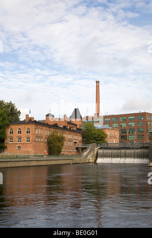 Red brick buildings - former industrial buildings - in the city of Tampere, Finland. The Tammerkoski Rapids can - Stock Photo