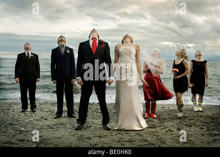 Wedding party on beach under threatening storm clouds - Stock Photo