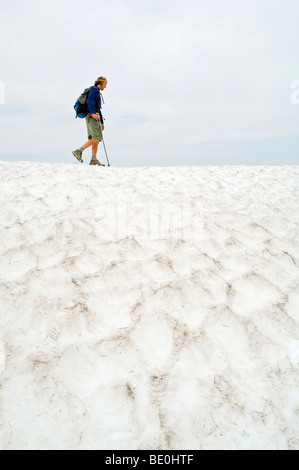 Eagle Cap Wilderness, Oregon, USA; Hiker on trail covered in summer snow - Stock Photo