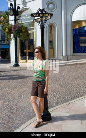 Woman posing in front of Via Rodeo sign, Rodeo Drive. Beverly Hills, Los Angeles, California, USA (MR) - Stock Photo