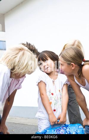 Young schoolgirl in the schoolyard, talking with older children - Stock Photo