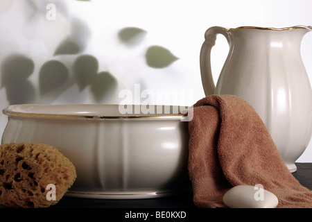 Old wash basin with towel, soap and sponge - Stock Photo