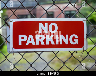 A No Parking sign hunging on a fence. - Stock Photo