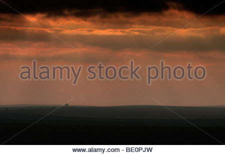 The sun creates an eerie glow through stormclouds over the mining landscape of Zennor moor - Stock Photo