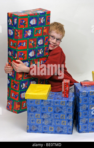 portrait of a young boy surrounded by Christmas presents - Stock Photo