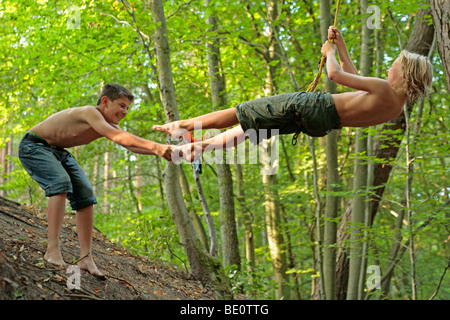 young boys playing in the woods - Stock Photo