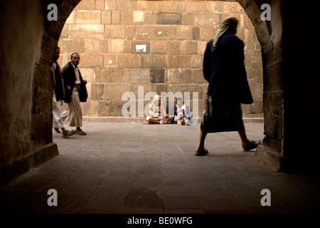 A pedestrian street scene in a back-alley in the old city of Sana'a, Yemen. - Stock Photo