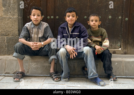 Three Yemeni children posing for a photo in the streets of old Sana'a, Yemen. - Stock Photo