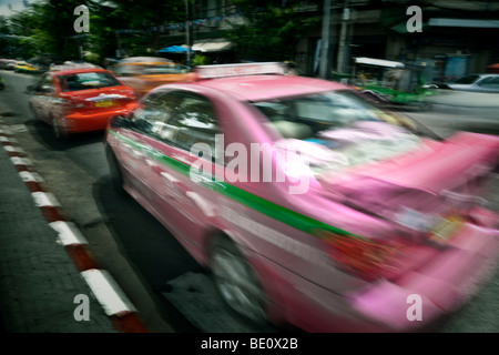 Thailand, Bangkok, hot pink taxi in blurred motion - Stock Photo