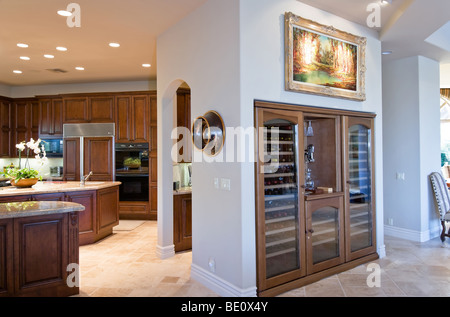 Side view of built-in wine bar adjacent to modern kitchen with dark wood cabinets - Stock Photo