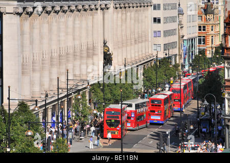 Oxford Street frontage of Selfridges department store with long queue of double decker red London buses at bus stops - Stock Photo