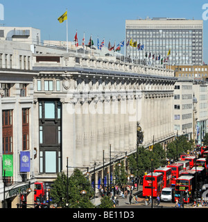 Oxford Street frontage of Selfridges department store with flags flying at roof top level & red London buses West End London England UK