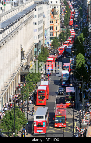 Looking down on UK Oxford Street with shoppers & aerial view of long queues of tfl double decker red London buses - Stock Photo