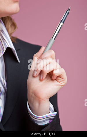 Detail shot of businesswoman's hand gesturing with pen - Stock Photo