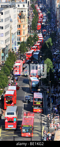 Looking down on UK London Oxford Street with shoppers & aerial views of long queues of double decker red London - Stock Photo
