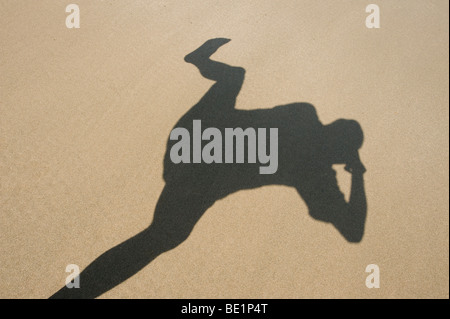 Funny shadow on a sandy beach of a photographer taking his own photograph - Stock Photo