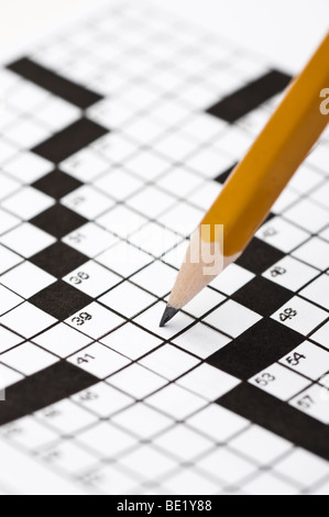 close up of a pencil solving a crossword puzzle - Stock Photo