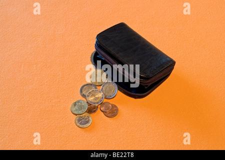 Half-open black leather purse with loose change spread out on an orange support. Porte-monnaie noir et menue monnaie. - Stock Photo