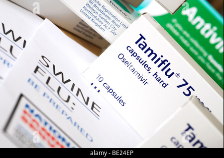 Several boxes of 10 capsule Tamiflu medication and Swine Flu information leaflets in the foreground - Stock Photo
