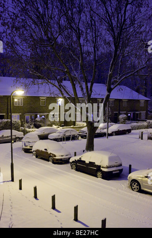 Heavy snow covers street in south London England. Cars sit quietly covered by snow and night has just begun to fall - Stock Photo