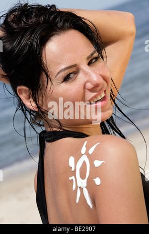 Portrait of attractive woman with sun-shaped sun cream - Stock Photo