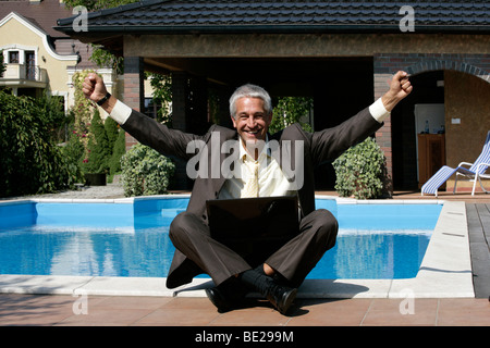 Happy businessman sitting next to the swimming pool - Stock Photo