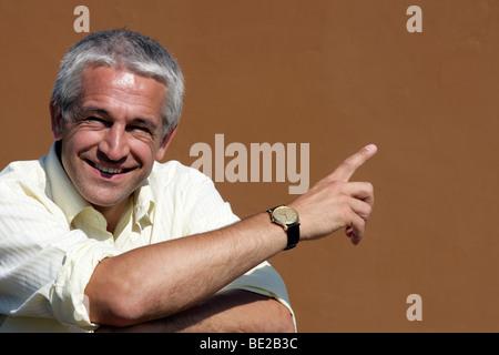 Portrait of happy businessman pointing - Stock Photo
