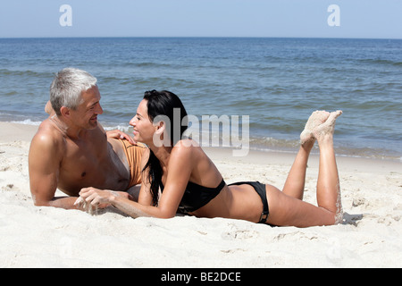 Attractive mature couple relaxing on the beach - Stock Photo