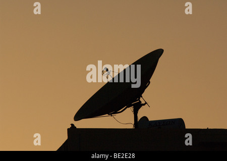 Satellite receiver dish in silhouette against an evening sky. - Stock Photo