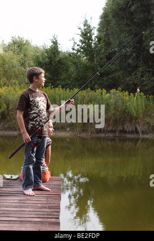 Young boy and girl children fishing on a wooden pier over a lake in summer - Stock Photo
