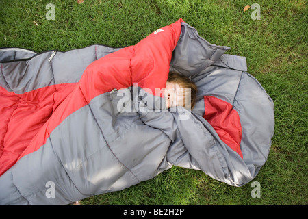 seven year old boy in a sleeping bag, laying down outdoors in a grass field - Stock Photo